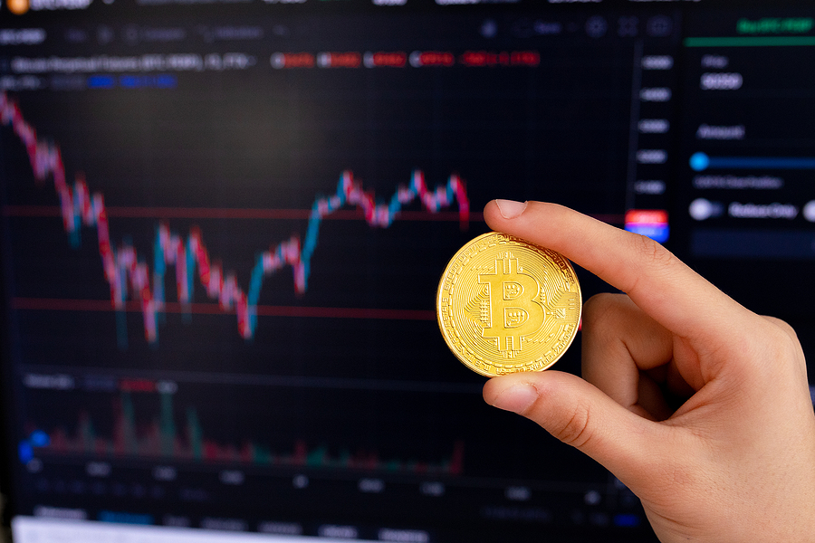 Hand holding bitcoin in front of the graph with the exchange rate. Bitcoin cryptocurrency gold coin. Trading on the cryptocurrency exchange. Bitcoin exchange rate trends. Bitcoin growth and fall charts.