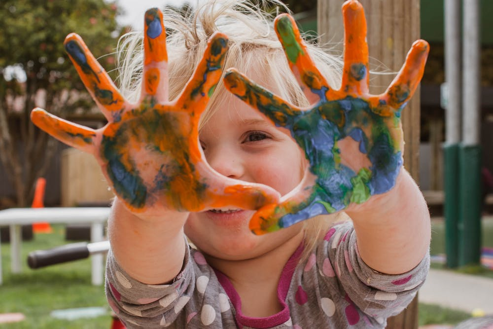 Little girl with paint in her hands